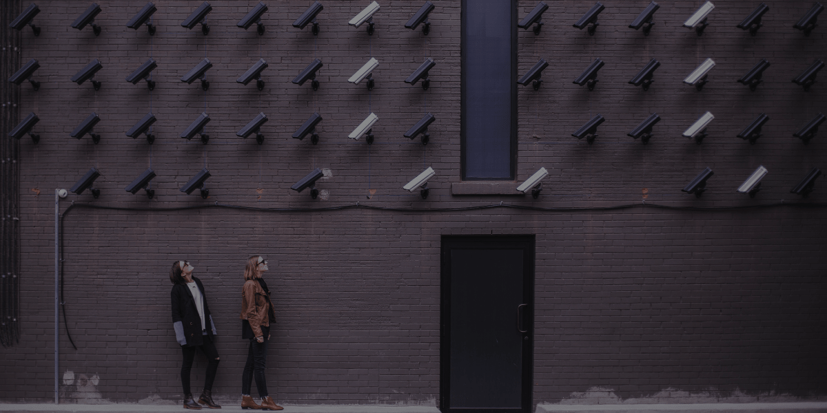 Two people staring up at security cameras.