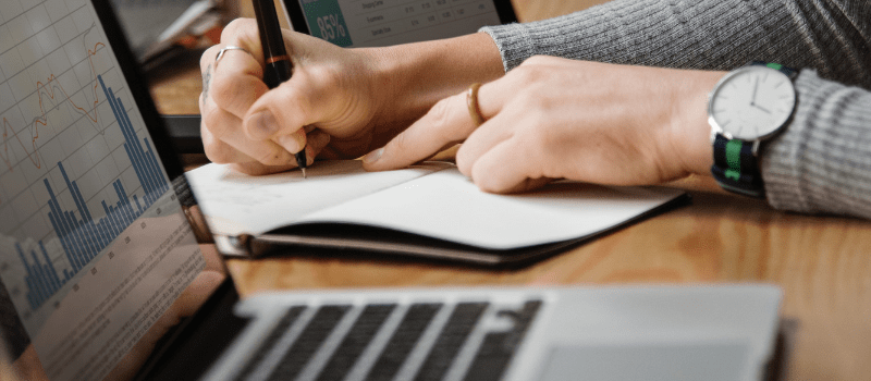 Two hands practising SEO writing on a notepad beside an open metal laptop on a wood grain desk.