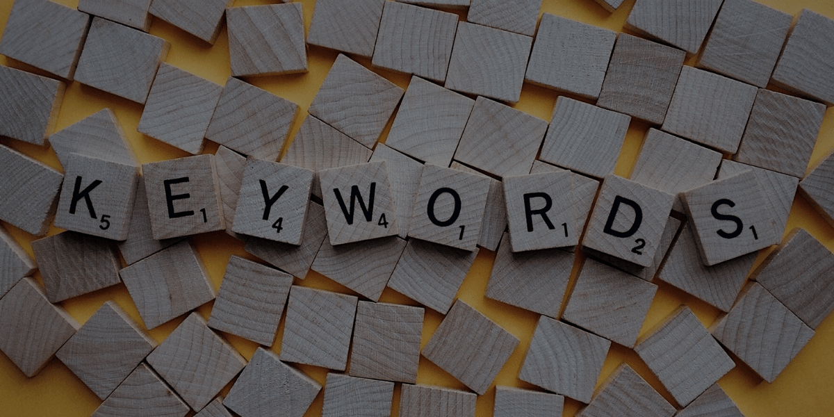 """Scrabble pieces spelling out """"what is a keyword?"""" on a yellow background."""